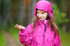 Adorable little girl playing happily in the rain Stock Photo