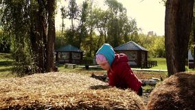 Adorable little girl playing in haystack on a warm autumn day stock video footage
