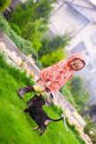 Adorable little girl playing with her puppy outdoor Stock Photography