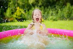 Adorable little girl playing in inflatable baby pool. Happy kid splashing in colorful garden play center on hot summer day. Summer activities for kids Stock Photography