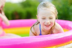 Adorable little girl playing in inflatable baby pool. Happy kid splashing in colorful garden play center on hot summer day. Summer activities for kids Royalty Free Stock Image