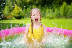 Adorable little girl playing in inflatable baby pool. Happy kid splashing in colorful garden play center on hot summer day. Summer activities for kids Royalty Free Stock Photos