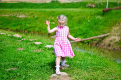 Adorable little girl playing by a lake in sunny park on a beautiful summer day Stock Photo