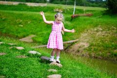Adorable little girl playing by a lake in sunny park on a beautiful summer day.  Royalty Free Stock Photos