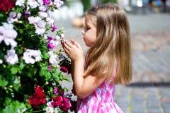 Adorable little girl playing near flower bush in a city park. Adorable little girl playing near flower bush Stock Photos
