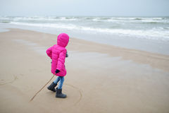 Adorable little girl playing by the ocean on winter day Stock Photo