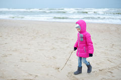 Adorable little girl playing by the ocean on winter day Royalty Free Stock Photography