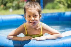 Adorable little girl playing at a outdoor swimming pool Royalty Free Stock Photos