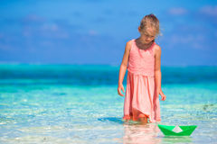 Adorable little girl playing with paper boat in Stock Image