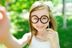 Adorable little girl playing with paper glasses on a stick Stock Photo