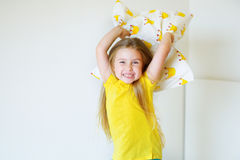 Adorable little girl playing with the pillow on the bed in her bedroom stock images