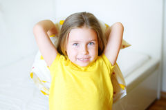 Adorable little girl playing with the pillow on the bed in her bedroom.  Stock Photography