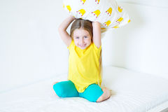 Adorable little girl playing with the pillow on the bed in her bedroom. Adorable little girl playing with the pillow on the bed Stock Image