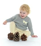 Adorable little girl playing with pine cones Stock Image