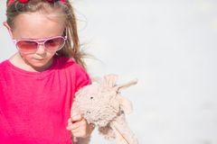 Adorable little girl playing with plush toy on Stock Photos