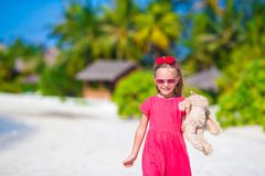 Adorable little girl playing with plush toy on Stock Images