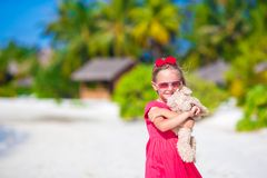 Adorable little girl playing with plush toy on Royalty Free Stock Image