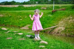 Adorable little girl playing by a pond in sunny park. Adorable little girl playing by a pond Royalty Free Stock Photography