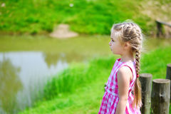Adorable little girl playing by a pond in sunny park on a beautiful summer day Stock Images