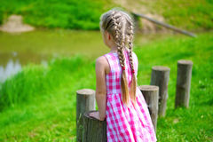 Adorable little girl playing by a pond in sunny park on a beautiful summer day. Adorable little girl playing by a pond in sunny park on summer day Royalty Free Stock Image
