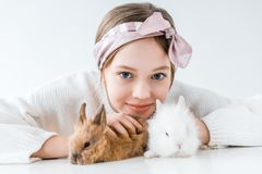 Adorable little girl playing with rabbits and smiling at camera. On white Royalty Free Stock Image
