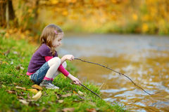 Adorable little girl playing by a river Stock Photography