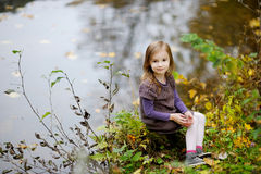 Adorable little girl playing by a river Stock Images