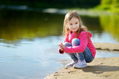 Adorable little girl playing by a river Royalty Free Stock Photo