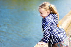 Adorable little girl playing by a river in sunny park on a beautiful summer day.  Royalty Free Stock Photography