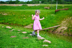 Adorable little girl playing by a river in sunny park on a beautiful summer day.  Royalty Free Stock Photos