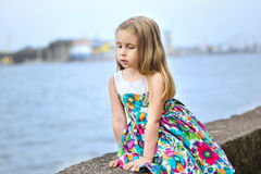 Adorable little girl playing by a river in sunny park on a beautiful summer day. Adorable little girl playing by a river in sunny park Royalty Free Stock Image