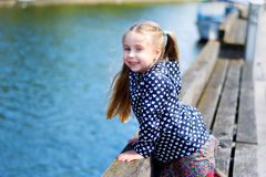 Adorable little girl playing by a river in sunny park on a beautiful summer day Stock Images
