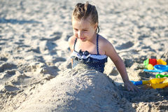 Adorable little girl playing with sand at the beach in summer. Adorable little girl playing with sand at the beach Royalty Free Stock Photo