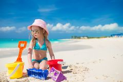 Adorable little girl playing with sand on a Royalty Free Stock Image