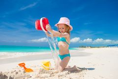 Adorable little girl playing with sand on a perfect tropical beach Stock Photos