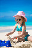 Adorable little girl playing with sand on a perfect tropical beach Stock Image