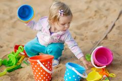 Adorable little girl playing with sand. On playground Stock Photos