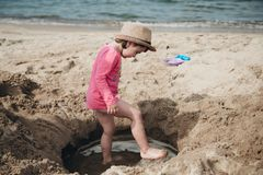 Adorable little girl playing with sand on the sea stock images