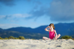Adorable little girl playing on a sandy beach Royalty Free Stock Photos