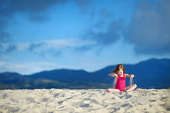 Adorable little girl playing on a sandy beach Royalty Free Stock Photo