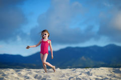 Adorable little girl playing on a sandy beach Stock Image