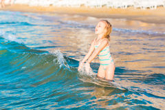 Adorable little girl playing in the sea on a beach Stock Image