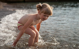 Adorable little girl playing on the seashore Stock Photos