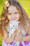 Adorable little girl playing with small kittens at summer day. Adorable little cyrly girl playing with small kittens at warm and sunny summer day. Happy smiling Stock Images
