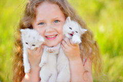 Adorable little girl playing with small kittens at summer day. Adorable little cyrly girl playing with small kittens at warm and sunny summer day. Happy smiling Royalty Free Stock Photography