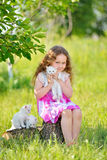 Adorable little girl playing with small kittens at summer day. Adorable little cyrly girl playing with small kittens at warm and sunny summer day. Happy smiling Royalty Free Stock Image