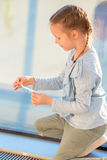 Adorable little girl playing with small model airplane in airport waiting for boarding Royalty Free Stock Photo