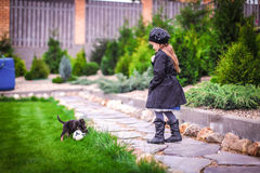 Adorable little girl playing with small puppy in the garden Royalty Free Stock Photos