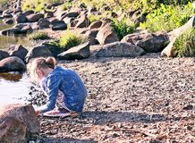 Adorable little girl playing with small stones on the river coast at spring. Adorable little girl playing with small stones on the river coast at spring stock photo