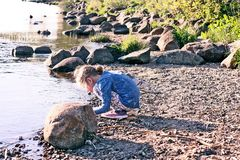 Adorable little girl playing with small stones on the river coast at spring. Adorable little girl playing with small stones on the river coast at spring stock photography